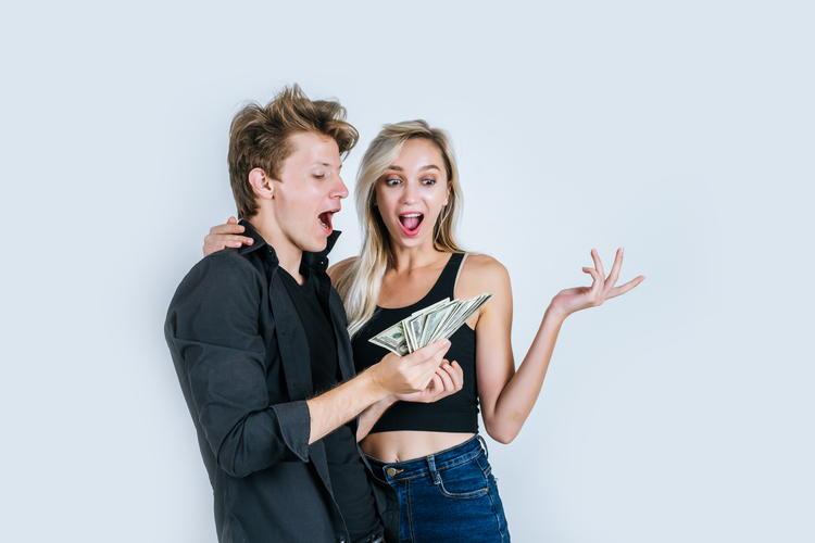 配当金:ドル紙幣を握りしめるカップル