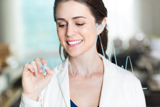 ガラスに株価チャートを描く女性